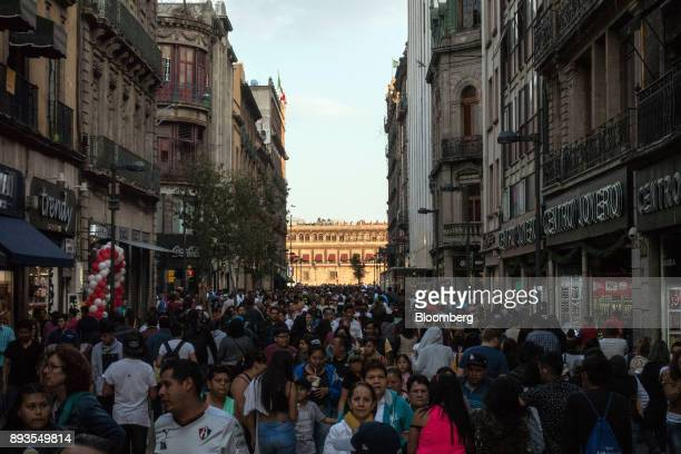 Pedestrians pass in front of retail stores and restaurants in Mexico City Mexico on Monday Nov 20 2017 The National Institute of Statistics and...