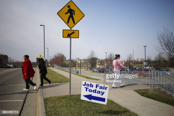 Pedestrians pass in front of signage displayed outside a Job News USA career fair in Overland Park Kansas US on Wednesday March 8 2017 Applications...