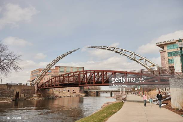 Pedestrians pass in front of the Arc of Dreams statue in Sioux Falls South Dakota US on Wednesday April 15 2020 South Dakota Governor Kristi Noem has...