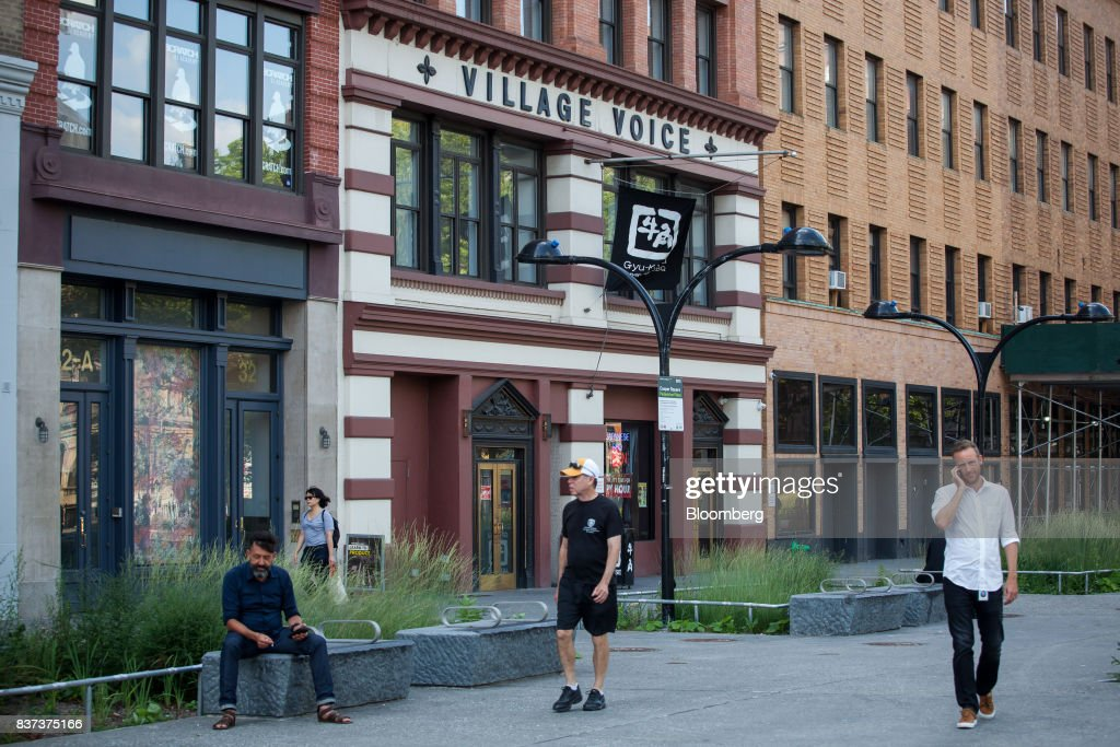 Pedestrians pass in front of the former headquarters for The Village Voice in the East Village neighborhood of New York, U.S., on Tuesday, Aug. 22, 2017. Peter Barbey, owner of The Village Voice since 2015, has decided to no longer produce a print edition of the alt-weekly publication. The company's announcement, made Tuesday afternoon, came as a surprise, a shock and a disappointment to the larger media industry on Twitter. Photographer: Michael Nagle/Bloomberg via Getty Images