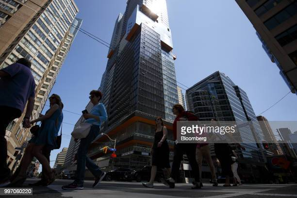 Pedestrians pass in front of the GWL Realty Advisors Livmore luxury apartment building stands under construction in Toronto Ontario Canada on Tuesday...