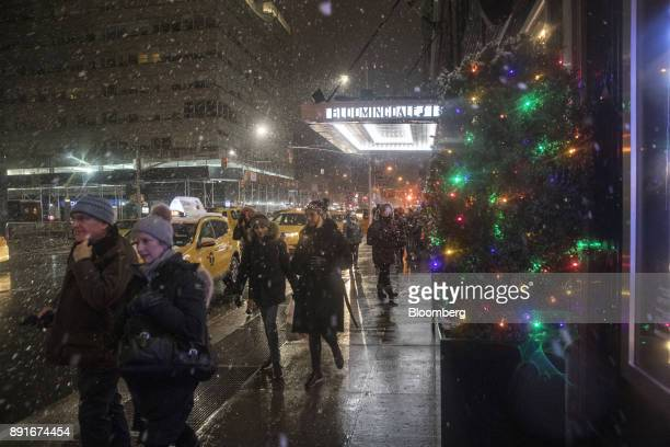 Pedestrians pass in front of the holiday decorations on display at the Bloomingdale's Inc department store in New York US on Saturday Dec 9 2017...