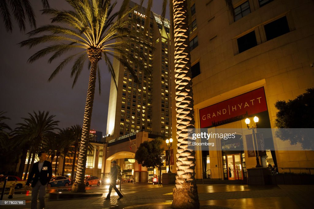 Pedestrians pass in front of the Manchester Grand Hyatt Hotel at night in San Diego, California, U.S., on Sunday, Feb. 11, 2018. Hyatt Hotels Corp. is scheduled to release earnings figures on February 14. Photographer: Patrick T. Fallon/Bloomberg via Getty Images