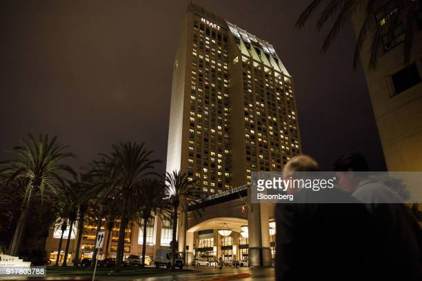 Pedestrians pass in front of the Manchester Grand Hyatt Hotel at night in San Diego California US on Sunday Feb 11 2018 Hyatt Hotels Corp is...