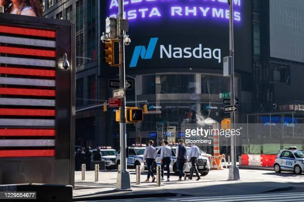 Pedestrians pass in front of the Nasdaq MarketSite in New York, U.S., on Monday, Nov. 9, 2020. Stockssurged around the world and bonds tumbled after...