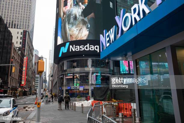 Pedestrians pass in front of the Nasdaq MarketSite in New York, U.S., on Monday, Dec. 21, 2020. Tesla Inc.'s was among the biggest drags on the S&P...