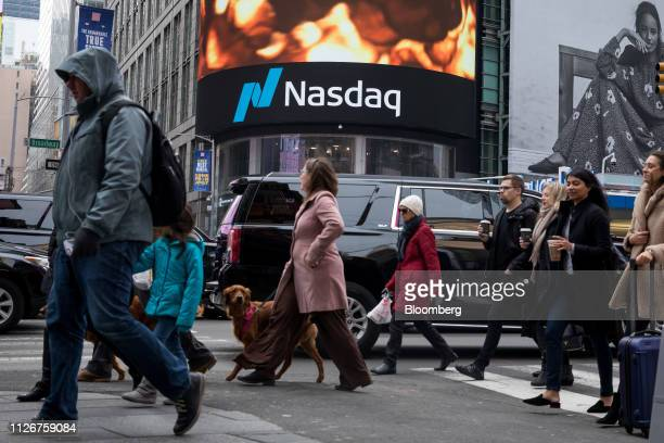 Pedestrians pass in front of the Nasdaq MarketSite in the Times Square neighborhood of New York US on Friday Feb 22 2109 US stocks rose along with...