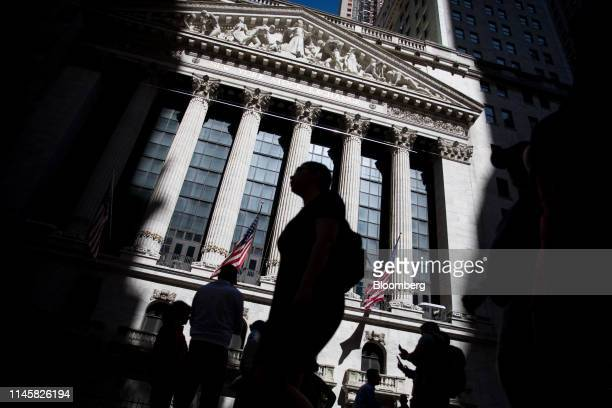 Pedestrians pass in front of the New York Stock Exchange in New York, U.S., on Friday, May 24, 2019. U.S. Equities climbed at the end of a bruising...