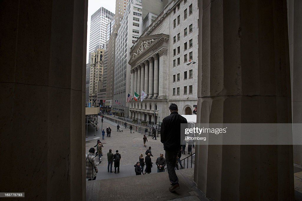 Pedestrians pass in front of the New York Stock Exchange (NYSE) in New York, U.S., on Friday, March 15, 2013. U.S. stocks fell, sending the Dow Jones Industrial Average lower for the first time in 11 days, as a report showed consumer confidence unexpectedly fell in March. Photographer: Scott Eells/Bloomberg via Getty Images