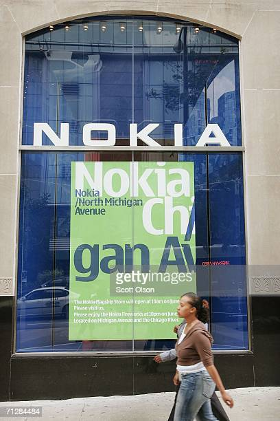 Pedestrians pass in front of the Nokia Flagship Store June 23 2006 in Chicago Illinois The store which is the first to open in the United States and...