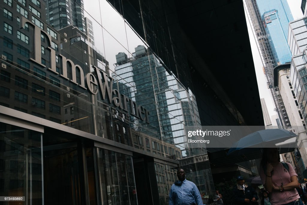 Pedestrians pass in front of the Time Warner Center in New York, U.S., on Wednesday, June 13, 2018. AT&T Inc.'s sweeping court victory allowing its takeover of Time Warner Inc. delivers a sharp setback to the Justice Department's new approach to policing mergers under President Donald Trump and promises to spark a merger wave across industries. Photographer: Christopher Lee/Bloomberg via Getty Images