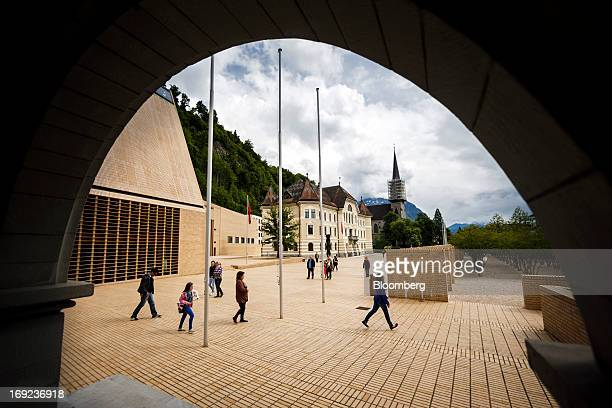 Pedestrians pass Liechtenstein's parliament, left, and government building, center, as they cross Peter-Kaiser Platz square in Vaduz, Liechtenstein,...