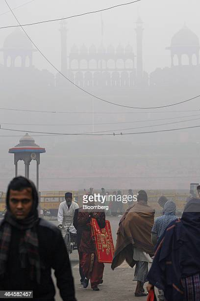Pedestrians pass police barricades in front of the Red Fort shrouded in haze in New Delhi India on Monday Jan 20 2014 India China and Brazil three of...