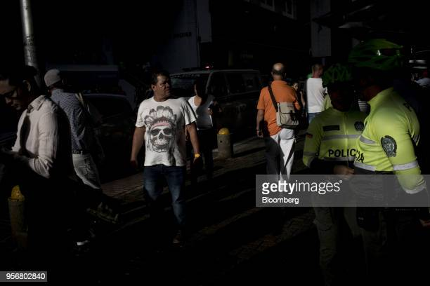 Pedestrians pass police officers in Bolivar Square as Gustavo Petro presidential candidate for the Progressivists Movement Party holds a campaign...