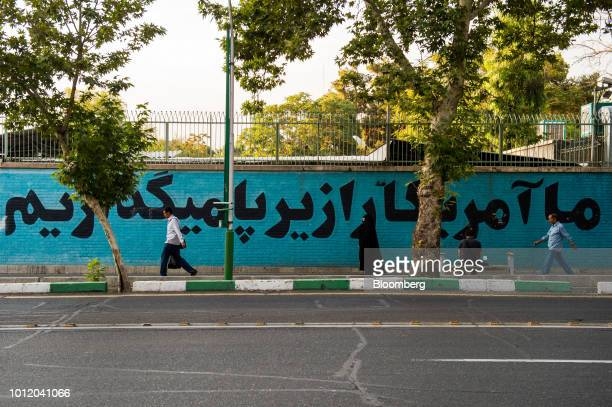 Pedestrians pass political wall murals on the wall of the former US embassy in Tehran Iran on Sunday Aug 5 2018 Irans central bank acting on the eve...