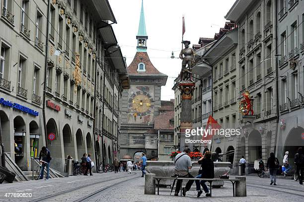 Pedestrians pass retail stores as the Zytglogge clock tower stands beyond in Bern Switzerland on Thursday June 18 2015 Swiss consumer prices are...