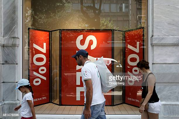 Pedestrians pass sale signs advertising 70% sales discounts in the window of a Hennes Mauritz AB fashion store in Thessaloniki Greece on Tuesday July...