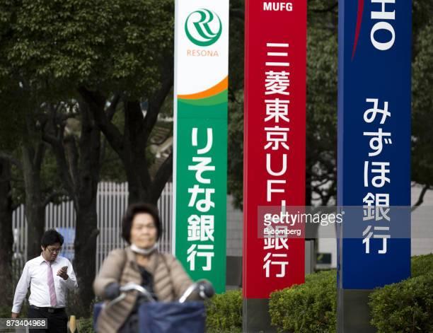 Pedestrians pass signage for Resona Bank Ltd from left Bank of TokyoMitsubishi UFJ Ltd and Mizuho Bank Ltd in Tokyo Japan on Friday Nov 10 2017...