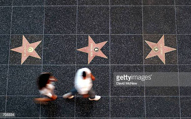 Pedestrians pass stars on the Walk of Fame sidewalk on Hollywood Boulevard next to the new Hollywood and Highland complex March 6 2002 in Hollywood...