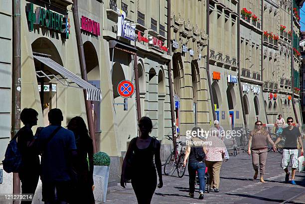Pedestrians pass stores on the Marktgasse street in Bern Switzerland on Tuesday Aug16 2011 The franc strengthened after the Swiss central bank...