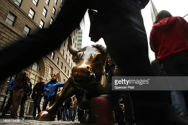 Pedestrians pass the bronze Charging Bull sculpture next to Wall Street in the Financial District on October 10 2013 in New York City The Dow Jones...