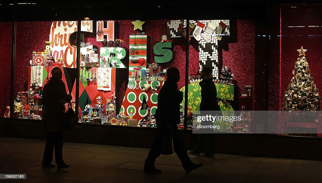 Pedestrians pass the Christmas window display of the Morelys department store in the Brixton district of south London, U.K., on Monday, Dec. 17, 2012. Retailers are relying on Christmas sales to help rescue a year when high unemployment and the debt crisis have blighted spending. Photographer: Simon Dawson/Bloomberg via Getty Images