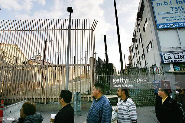 Pedestrians pass the fortified border fences as they cross over the international border from Mexico to the United States on the morning that the US...