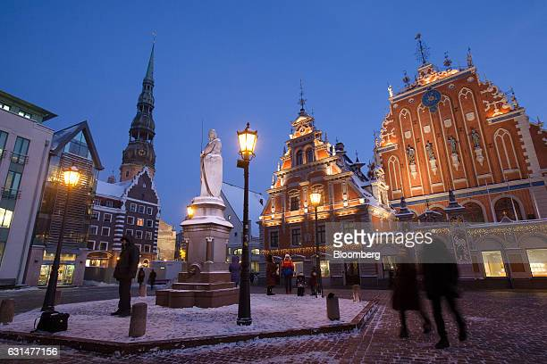 Pedestrians pass the House of Blackheads and a statue of Roland onTown Hall square in the old town in Riga Latvia on Tuesday Jan 10 2017 In 2016 the...