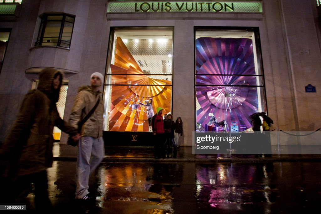 Pedestrians pass the illuminated window display of a Louis Vuitton store, operated by LVMH Moet Hennessy Louis Vuitton SA, on the Champs-Elysees in Paris, France, on Saturday, Dec. 15, 2012. The French minister for energy and environment unveiled a proposal for lights in and outside shops, offices, and public buildings -- including the flagship Louis Vuitton store and the Lido cabaret house on Paris's Avenue des Champs Elysees -- to be turned off between 1 a.m. and 7 a.m. starting in July. Photographer: Balint Porneczi/Bloomberg via Getty Images
