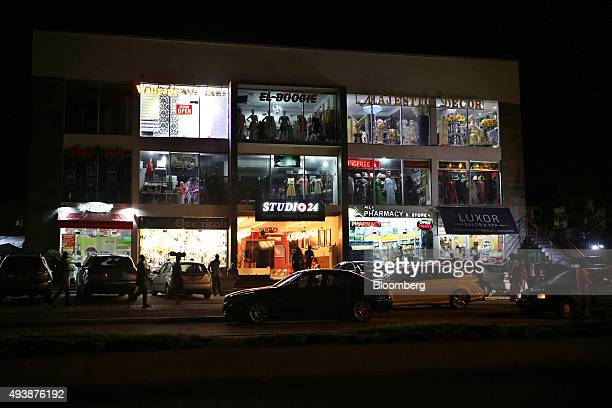 Pedestrians pass the illuminated windows of retail outlets in a shopping center at night in Abuja Nigeria on Wednesday Oct 21 2015 A drop in crude...