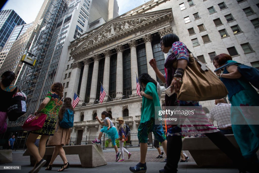 Pedestrians pass the in front of the New York Stock Exchange (NYSE) in New York, U.S., on Monday, Aug. 21, 2017. U.S. stocks fluctuated after erasing early losses, while the dollar edged lower amidgrowing uneaseabout persistent low inflation and as investors await central bank speeches at Jackson Hole. Photographer: Michael Nagle/Bloomberg via Getty Images