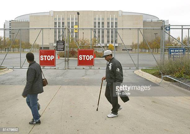 Pedestrians pass the locked gate of a parking area at the back of the United Center home of the NHL Chicago Blackhawks hockey team October 14 2004 in...