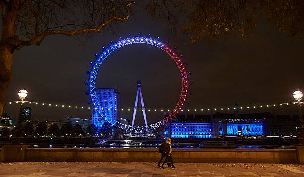 Pedestrians P The London Eye Illuminated In Blue White And Red Lights Resembling Colours Of