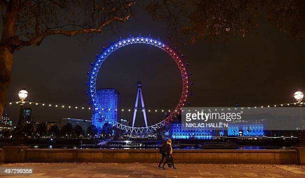 Pedestrians pass the London Eye illuminated in blue white and red lights resembling the colours of the French national flag in central London on...