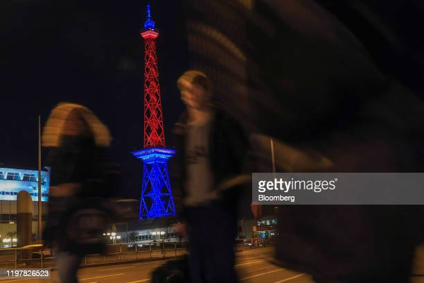 Pedestrians pass the Radio Tower which has been illuminated in red and blue to mark the day the UK leaves the European Union in Berlin Germany on...
