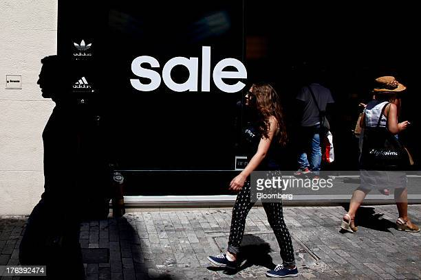 Pedestrians pass the window of a store advertising a sale and Adidas AG logos in Athens Greece on Friday Aug 9 2013 Greece's economy contracted for a...