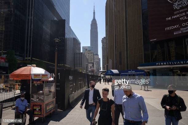 Pedestrians pass through a square outside Pennsylvania station before the Empire State building in central Manhattan, New York city on May 19, 2021....