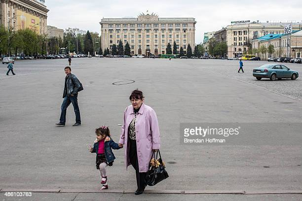 Pedestrians pass through Freedom Square where the regional administration buildng which was briefly occupied earlier this month is visible in the...