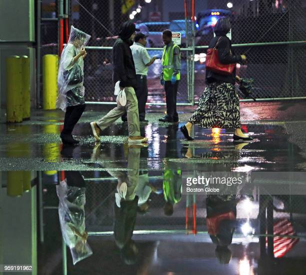 Pedestrians pass through large puddles outside of TD Garden in Boston during heavy rainfall from an afternoon thunderstorm on May 15 2018