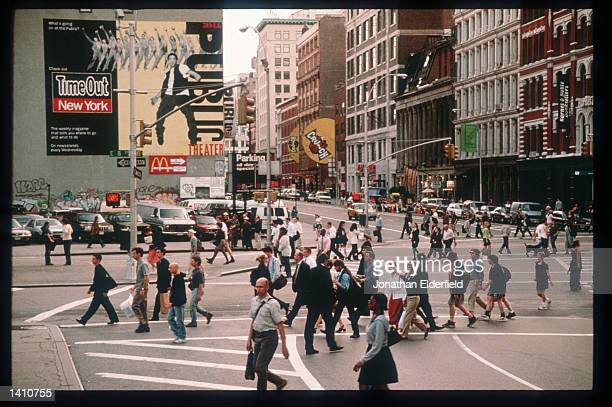 Pedestrians pass through the intersection of East Eighth Street, Lafayette Street and Astor Place in the East Village June 1, 1998 in New York City....