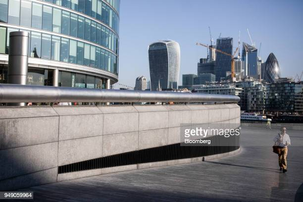 Pedestrians pass through the More London office space in view of 20 Fenchurch Street also known as the 'WalkieTalkie' and construction in the City of...