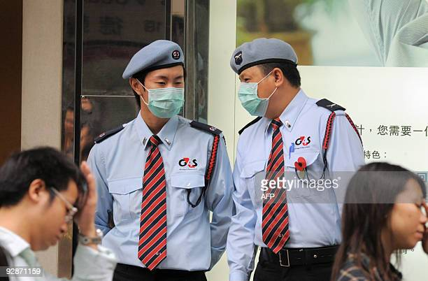 Pedestrians pass two security guards wearing protective face masks outside a high street bank in the Central district of Hong Kong on November 7 2009...