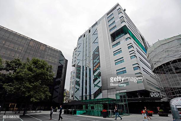 Pedestrians pass UBS AG's Finsbury Avenue office building left as construction work continues on the company's new office complex center at No 5...