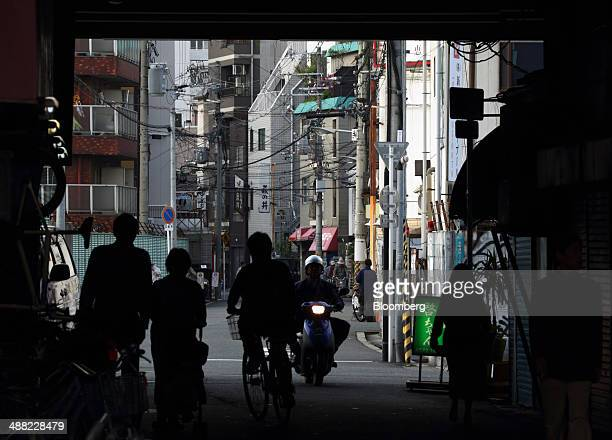 Pedestrians pass under raised railway tracks in the Airin area of Nishinari ward in Osaka Japan on Friday May 2 2014 Osaka prefecture's economic...