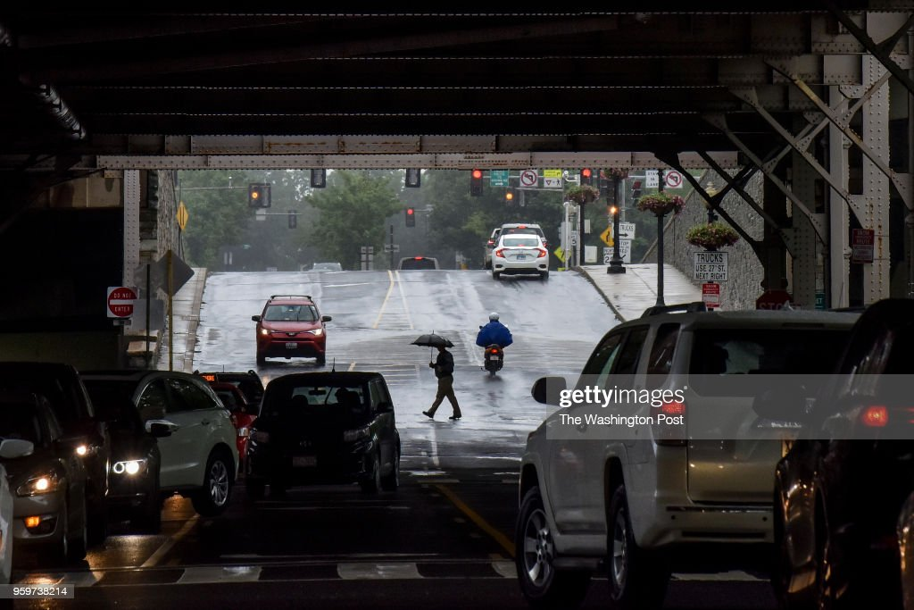 Pedestrians pass under the Whitehurst Freeway overpass as bands of rain move through the DC area on Thursday, May 17, 2018, in Washington, DC.