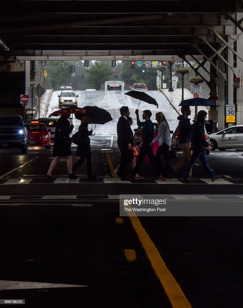 Pedestrians pass under the Whitehurst Freeway overpass as bands of rain move through the DC area on Thurssday, May 17, 2018, in Washington, DC.