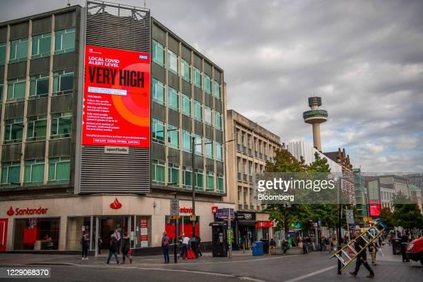 Pedestrians pass underneath a National Health Service covid-19 alert digital sign above a Banco Santander SA bank branch, as the region heads into a...
