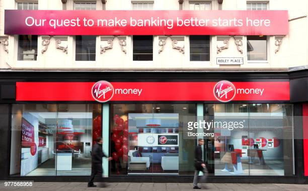 Pedestrians pass Virgin Money's first high street bank operated by Virgin Money Holdings UK Ltd in the former Northern Rock bank building in...