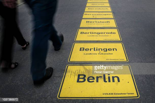 Pedestrians passing a line of about 11400 town signs of all municipalities in Germany on September 21 2018 in Berlin Germany On occasion of the...