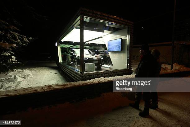 Pedestrians pause to look at an Audi Quattro V6T automobile manufactured by Audi AG as it stands displayed in a glass booth ahead of the World...